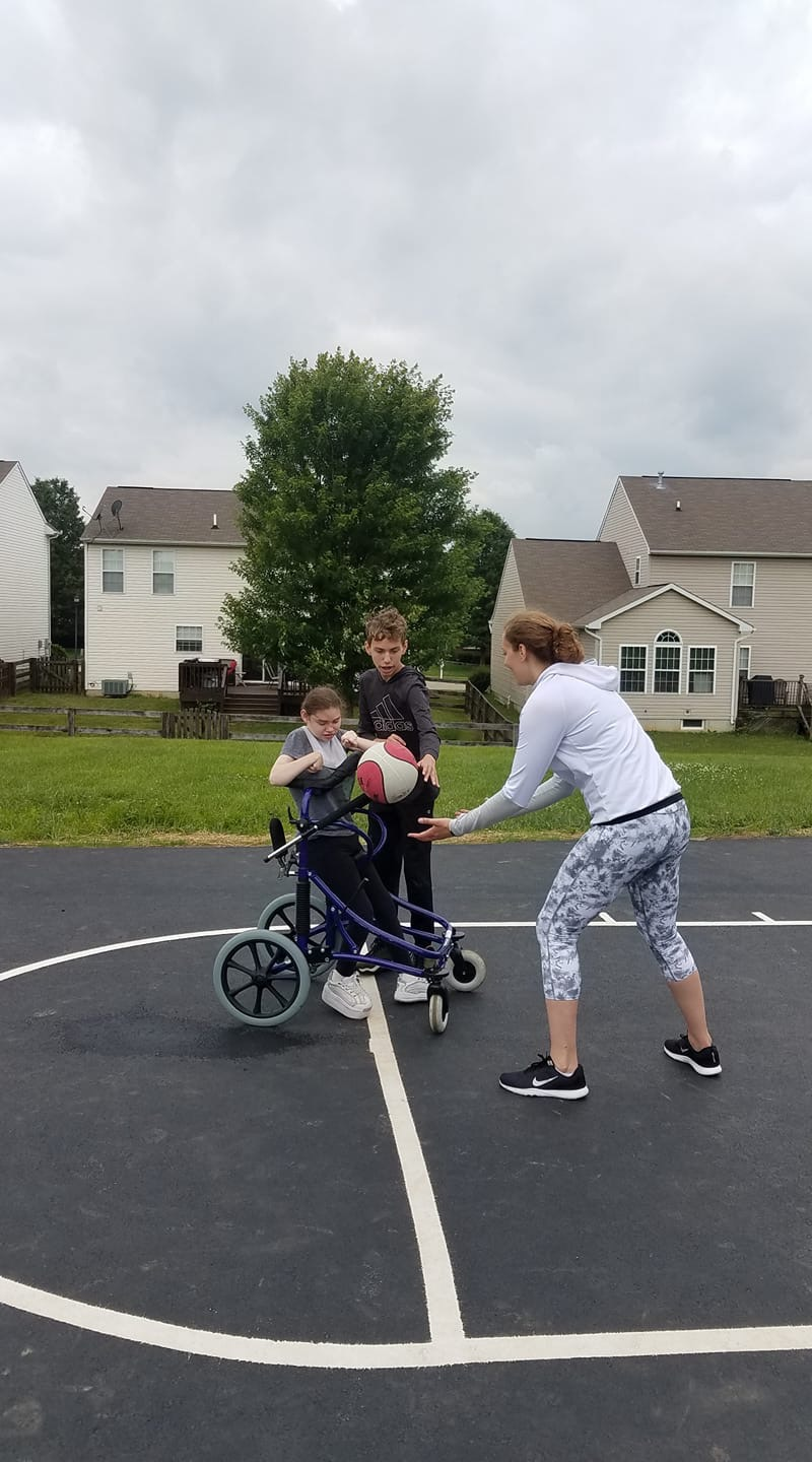 A woman in white playing basketball with her step brother and little sister in a walker.