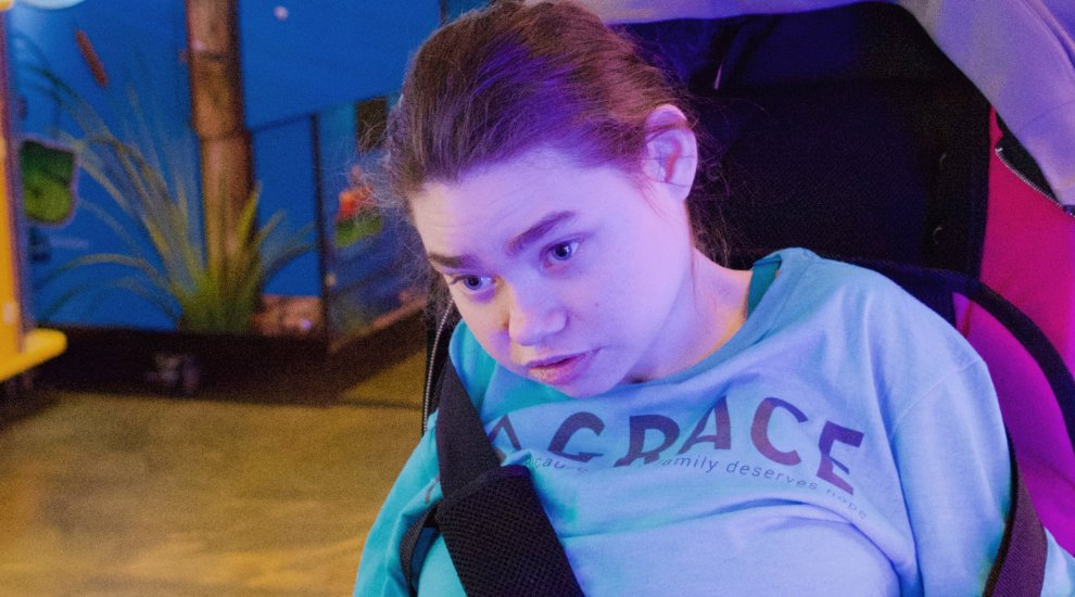 Teenager smiling while wearing a Grace shirt in a wheelchair.