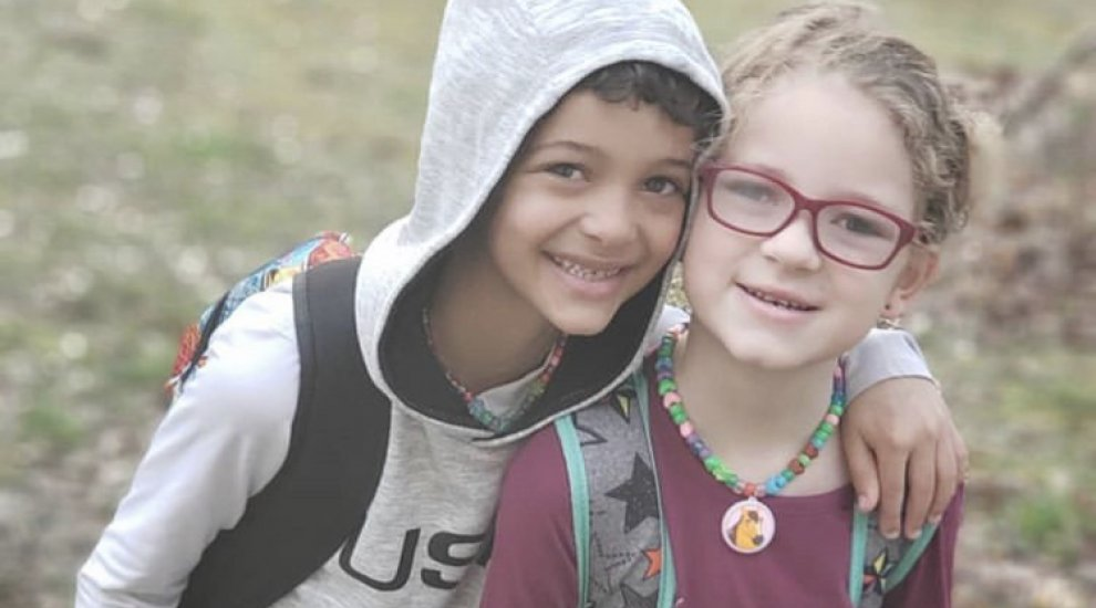 Young boy in gray hooding with his arm around his younger sister smiling.