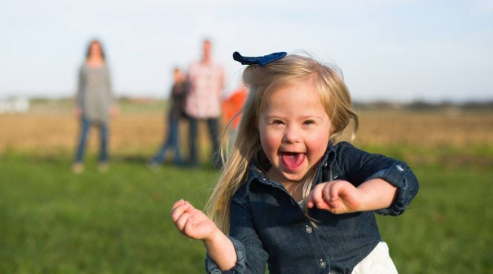 Young girl with down syndrome dancing in a field with her family behind her