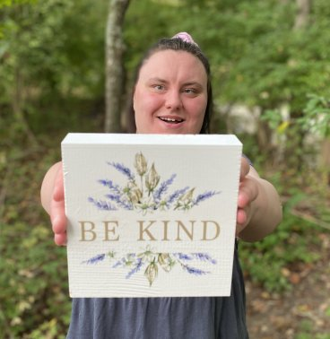"A woman with cerebral palsy holding a sign that says ""be kind""."