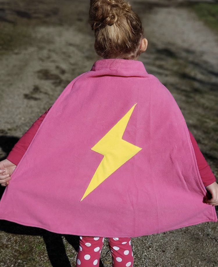 Little girl wearing a pink superhero cape with a yellow flash symbol on the back.